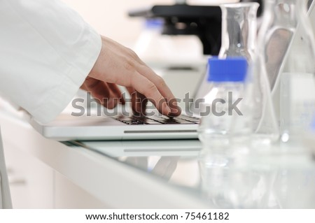 Working in lab with liquids and writing results on laptop, closeup Stock photo © zurijeta