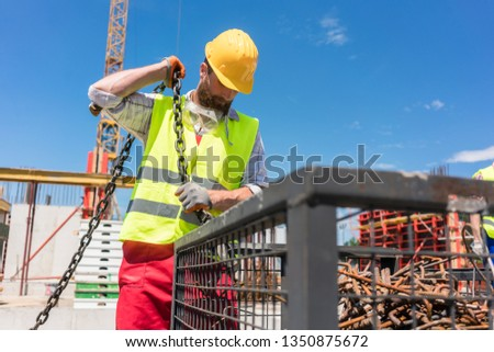 Reliable worker checking the safety latch of a hook before lifti Stock photo © Kzenon