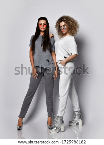 Two young women looking together at a trendy magazine during coffee break Stock photo © Kzenon