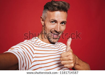 Joyous man in striped t-shirt smiling and showing thumb up while Stock photo © deandrobot
