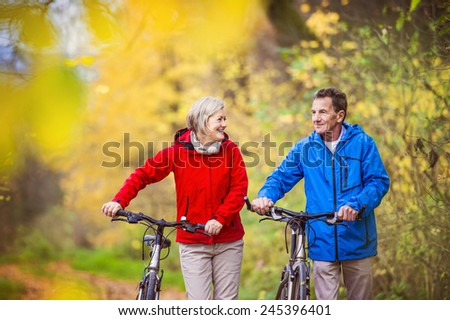 active senior couple together enjoying romantic walk with bicycl stock photo © boggy