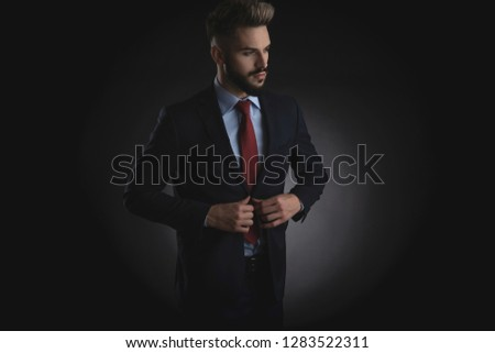 portrait of curious businessman buttoning navy suit while standi Stock photo © feedough