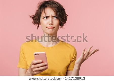 Verward jonge vrouw poseren geïsoleerd roze Stockfoto © deandrobot