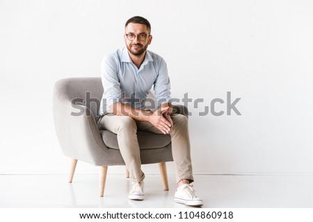 Portrait of attractive european man in formal wear sitting on ta Stock photo © deandrobot