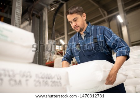 Young worker of polymer production factory loading sacks with plastic granules Stock photo © pressmaster
