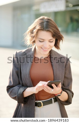 Young successful businesswoman in formalwear scrolling in mobile phone Stock photo © pressmaster