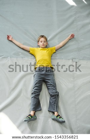 Fallen boy in activewear lying on grey mat after climbing practice Stock photo © pressmaster