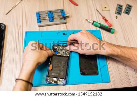 Hands of repairman with tweezers over demounted smartphone during repairing work Stock photo © pressmaster