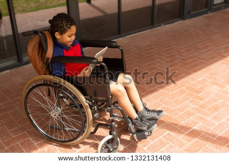 Side view of smiling mixed-raced disabled schoolboy using digital tablet in corridor at elementary s Stock photo © wavebreak_media