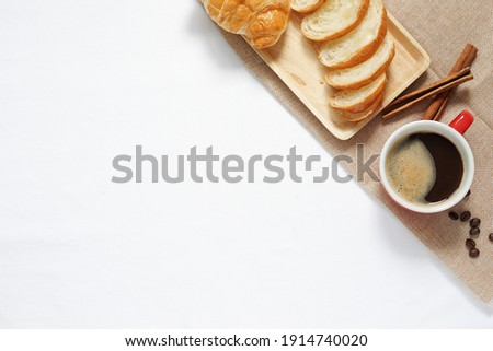Croissants on a ceramic plate, cinnamon sticks and coffee beans on a black wooden table. Stock photo © katya_sorokopudo