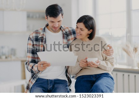 Caring man embraces his wife, look through documents with happy expressions, study payment bills, dr Stock photo © vkstudio