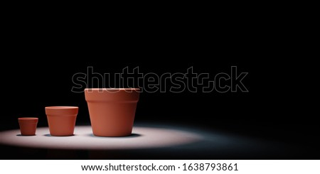 Increasing Size Empty Flowerpot Spotlighted on Black Background Stock photo © make
