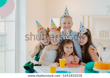 Photo of happy friends gather around table, wear party hats, embrace and look gladfully at camera, s Stock photo © vkstudio
