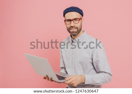 Talented male journalist with appealing look, holds modern laptop computer, works on new article, dr Stock photo © vkstudio