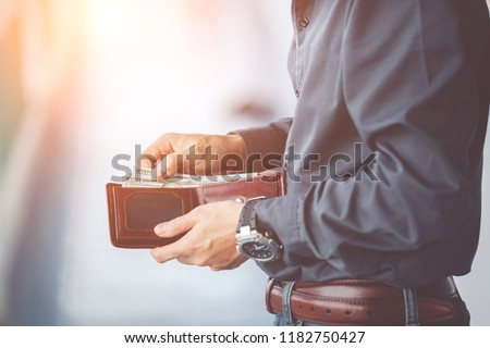 Man holding a wallet with  money dollars  in hand in black medical gloves. Stock photo © Illia