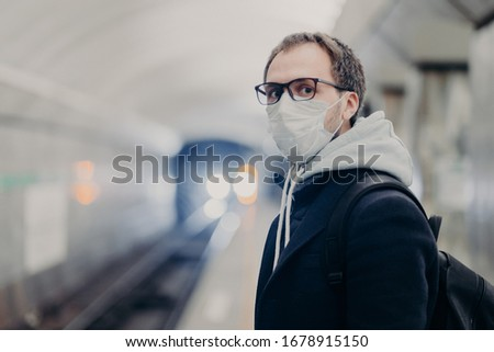 Coronavirus crisis. Male follows quarantine rules wears protective medical mask, travels in public t Stock photo © vkstudio