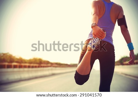 Stock photo: Sporty woman runner stretching legs for warming up before exercising