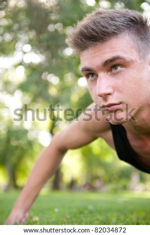 Portrait of young man full of attitude doing pushups on grass at Stock photo © HASLOO