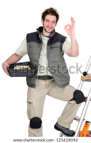 Stock photo: Approving tradesman posing with his tools and building materials