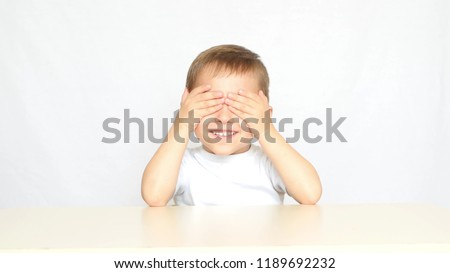 Portrait of little boy closing eyes with his hands at home playi Stock photo © HASLOO