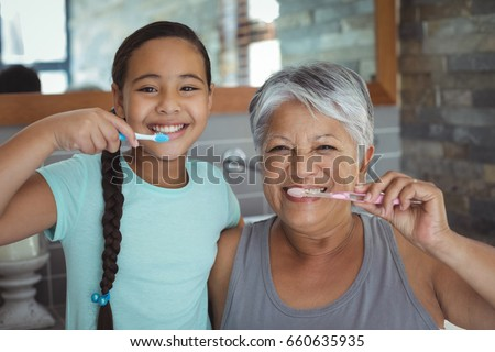 Grandmother Brushing Teeth In Bathroom With Granddaughter Watchi Stock photo © monkey_business