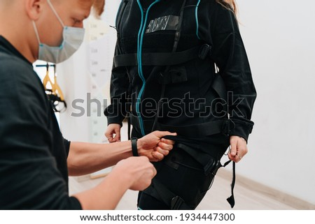Young woman putting on  Electro Muscular Stimulation EMS exercise training costume  Stock photo © Nejron