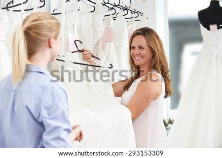 Sales Assistant In Bridal Store Helping Bride To Choose Wedding  Stock photo © HighwayStarz