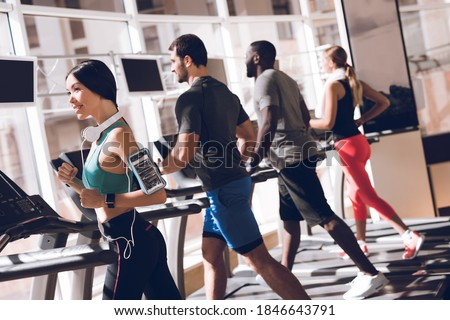 Pretty focused young woman athlete running on treadmill in gym Stock photo © deandrobot