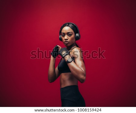 female boxer posing wearing red boxing gloves and sports gear stock photo © deandrobot
