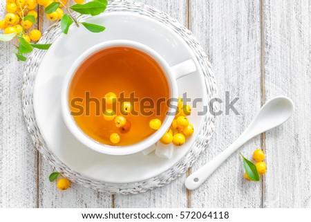 Fresh warmer herbal hawthorn tea with fresh berries in a white cup on wooden background, alternative Stock photo © yelenayemchuk