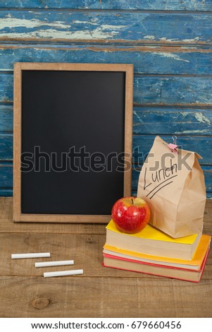slate with chalks by lunch bag and books on wooden table against library shelf stock photo © wavebreak_media