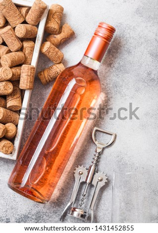 Bottle and glasses of pink rose wine with box of corks on stone kitchen table background. Top view.  Stock photo © DenisMArt