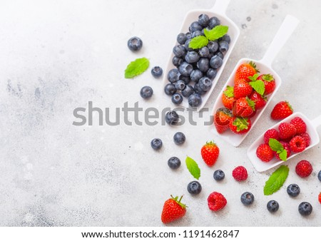 fresh raw organic berries in white scoop spoon on kitchen table backgroundtop view strawberry ras stock photo © denismart