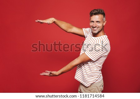 Joyous guy in striped t-shirt gesturing and demonstrating size w Stock photo © deandrobot