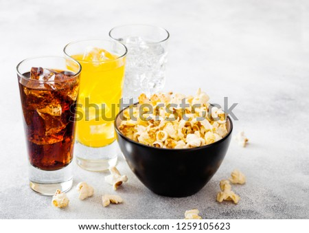 Glasses of soda drink with ice cubes and black bowl of popcorn snack on stone kitchen table backgrou Stock photo © DenisMArt