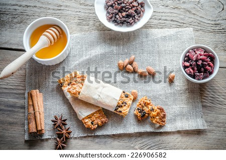 Organic cereal fruit granola bar with berries on vintage board with honey spoon and jar of oats on p Stock photo © DenisMArt