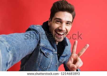Excited young man in jeans denim jacket take selfie by camera isolated over red background showing t Stock photo © deandrobot