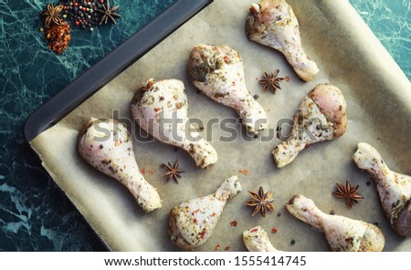 Stock photo: Baked chicken drumstick in a green dish with orange and rosemary