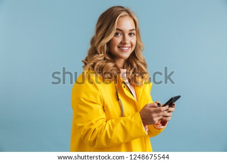 Image of young woman 20s wearing yellow raincoat holding mobile  Stock photo © deandrobot