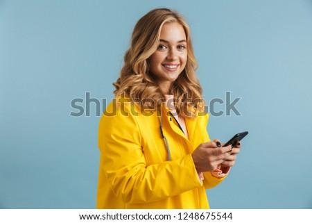 Kép fiatal nő 20-as évek visel citromsárga esőkabát Stock fotó © deandrobot