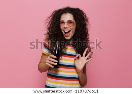 Photo of cheerful woman 20s with curly hair drinking soda from g Stock photo © deandrobot