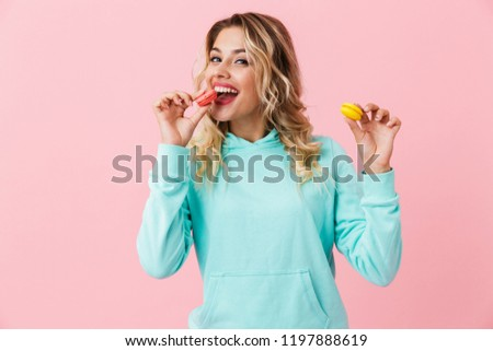 Photo of pretty woman in basic clothing eating two macaron biscu Stock photo © deandrobot