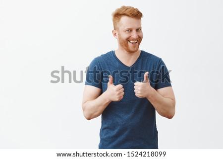 Сheerful handsome man smiling showing thumb up like gesture choosing five stars rating. Stock photo © ichiosea