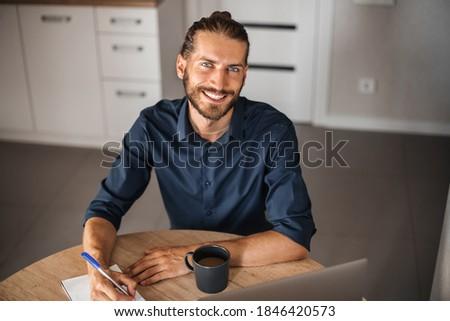 Sentado atractivo hombre escrito bloc de notas Foto stock © feedough