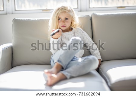 4 years old child watching tv laying down on the sofa at home alone Stock photo © Lopolo