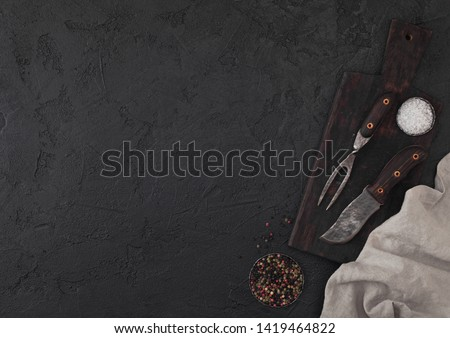 Vintage meat knife and fork and hatchet on black table background. Butcher utensils. Space for text Stock photo © DenisMArt