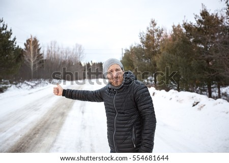 young handsome man in black jacket in winter, stood on the highway and hitchhiking. Stock photo © Lopolo