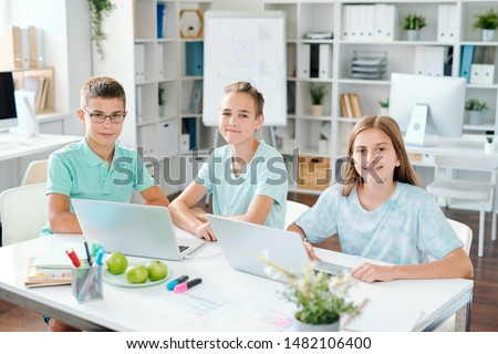 three diligent schoolchildren looking at you while sitting by desk stock photo © pressmaster