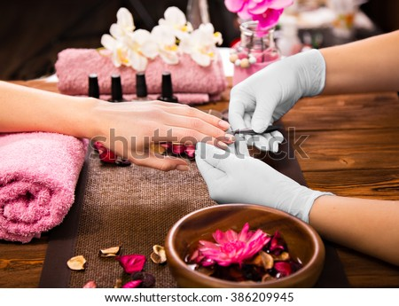 Closeup finger nail care by manicure specialist in beauty salon. Manicurist paints nails with nail p Stock photo © galitskaya
