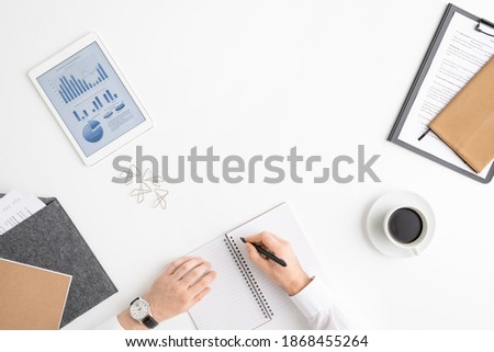 Overview of human hands with drink holding pen over blank page of copybook Stock photo © pressmaster